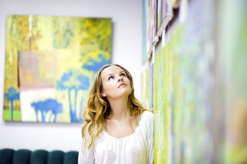 Woman gazing at artwork on the wall cm