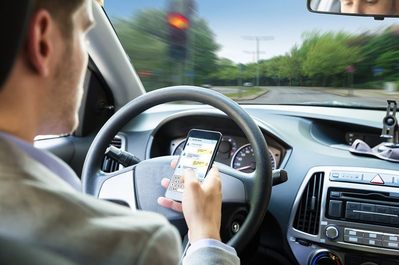 Person Sending Text Message By Mobile Phone While Driving Car cm
