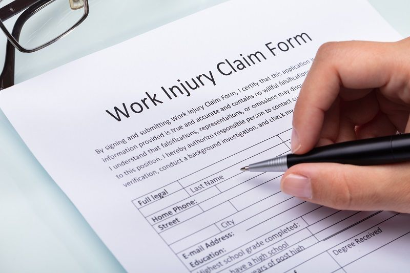 Woman Filling Work Injury Claim Form cm