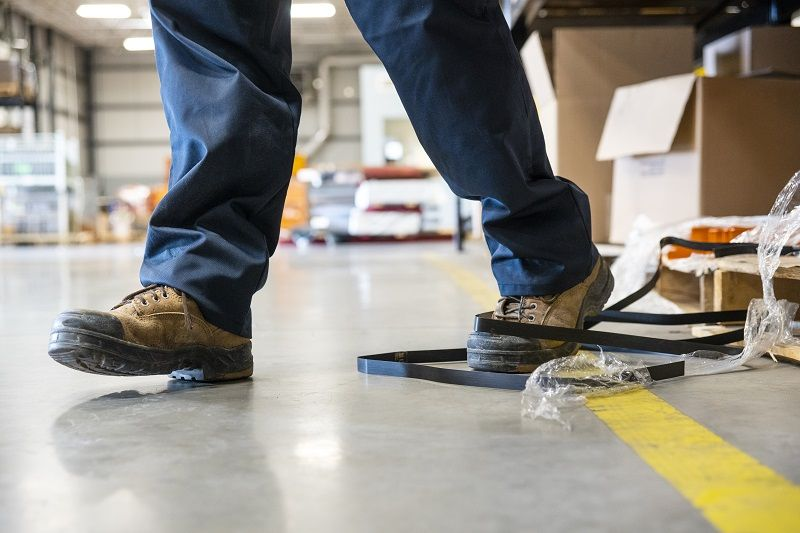An industrial safety topic. A worker tripping over a trash on a factory floor cm