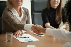 Diverse businesswomen shaking hands at group meeting or job interview cm 300x200